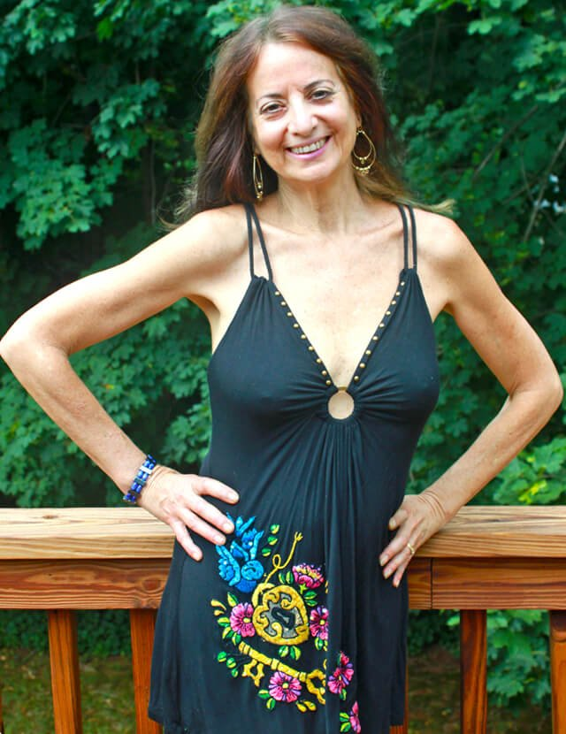 Karen Ranzi with her hands at her waist on a deck
