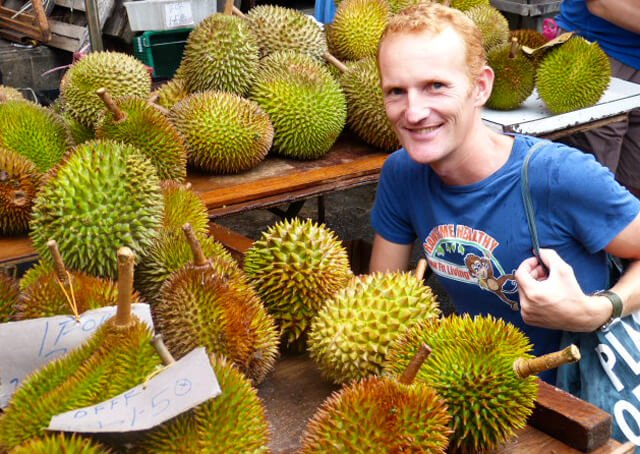 Paul Tarbath smiles in a durian market