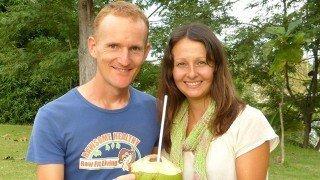 Paul and Yulia Tarbath pose while holding a coconut