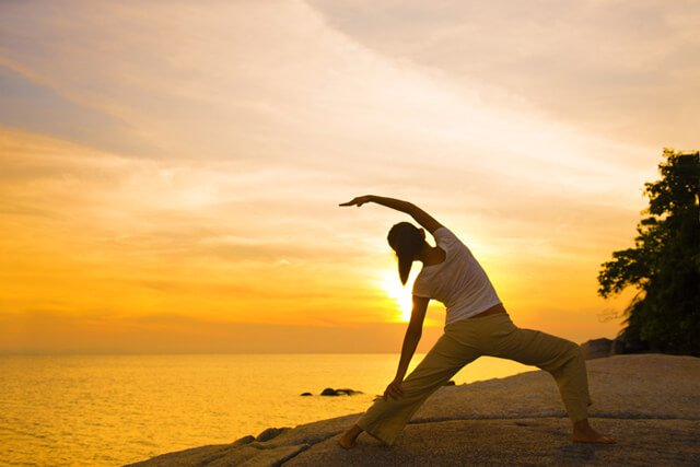 Woman in yoga pose at sunset overlooking the sea