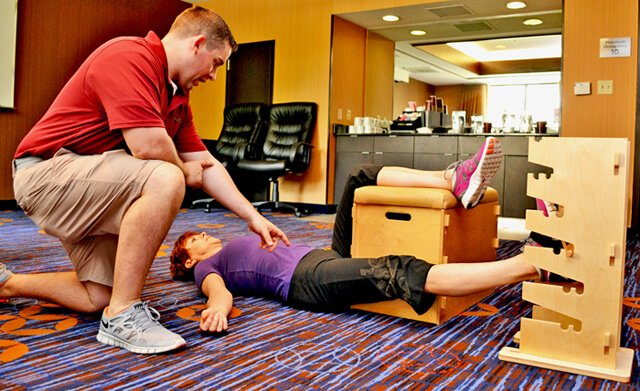 Joan Adams performs Progressive Supine Groin while Mike Kenny oversees