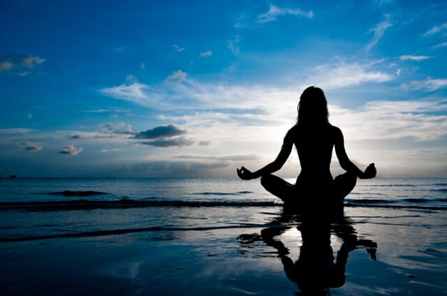 Silhouette of a woman meditating on a beach