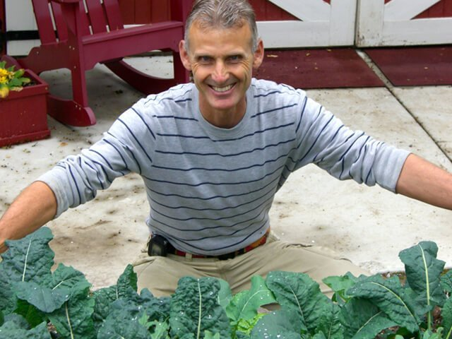 Don Weaver smiles while working in his garden full of greens