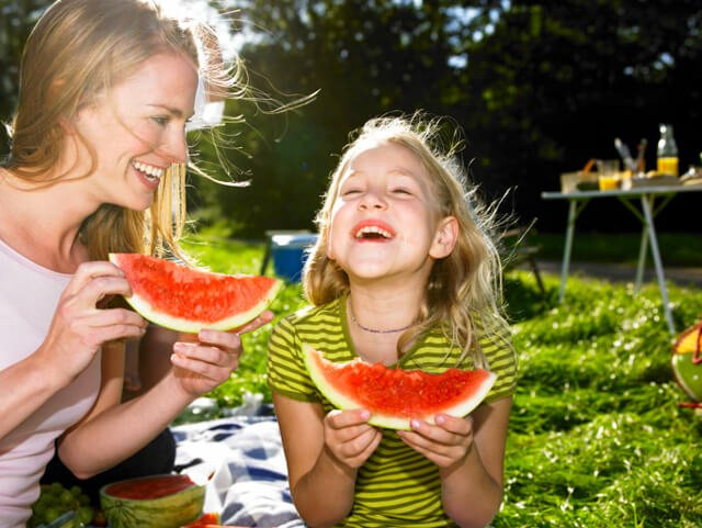 Mother and daughter enjoying watermelon outdoors