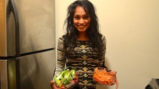 Silpa Reddy holds two dishes of food beside a refrigerator