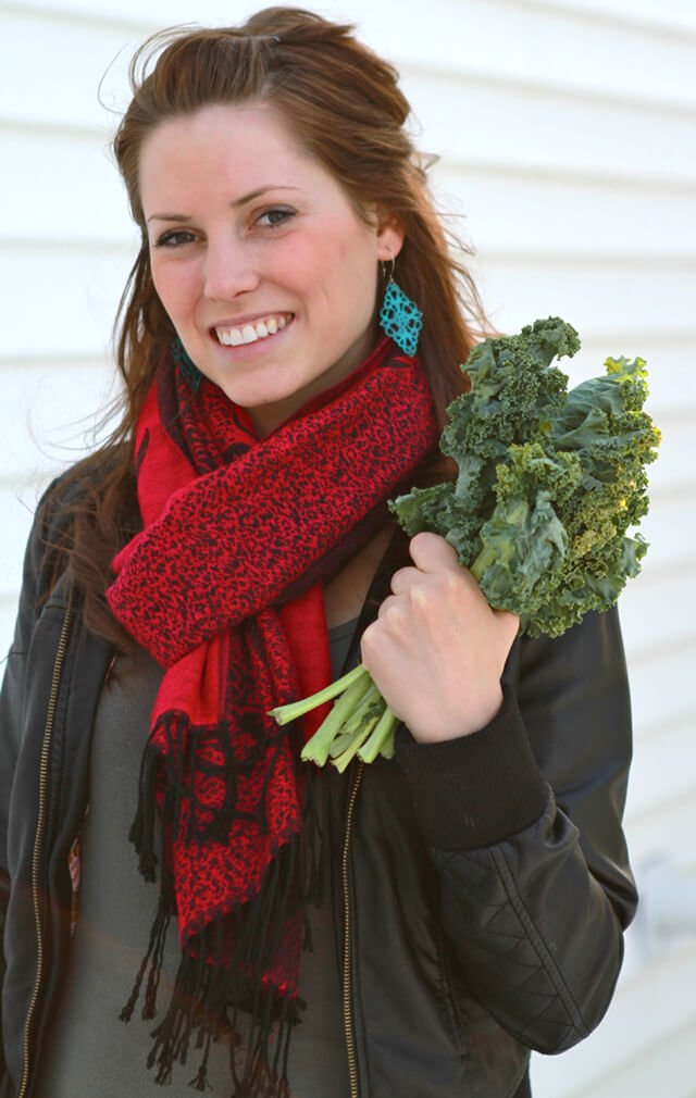 Ashley Clark holds a bunch of kale outside dressed in a winter coat