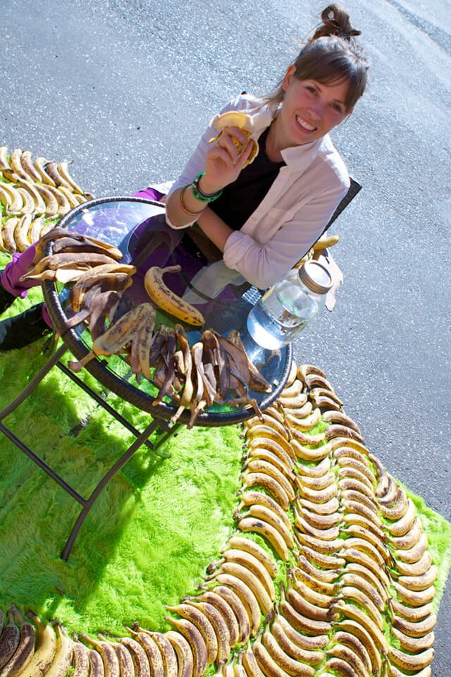 Ashley Clark is roadside and surrounded by bananas on a green carpet