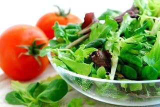 Salad of baby greens with tomatoes against a white background