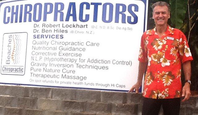 Robert Lockhart standing beside his chiropractic office sign