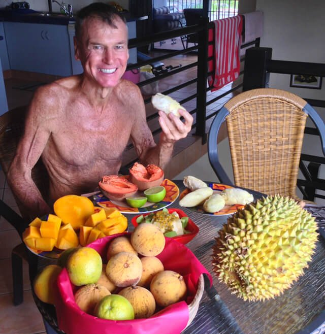 Robert Lockhart eats fruit on a dining room table