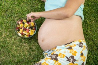 A pregnant woman eats fruit from a bowl on a lawn