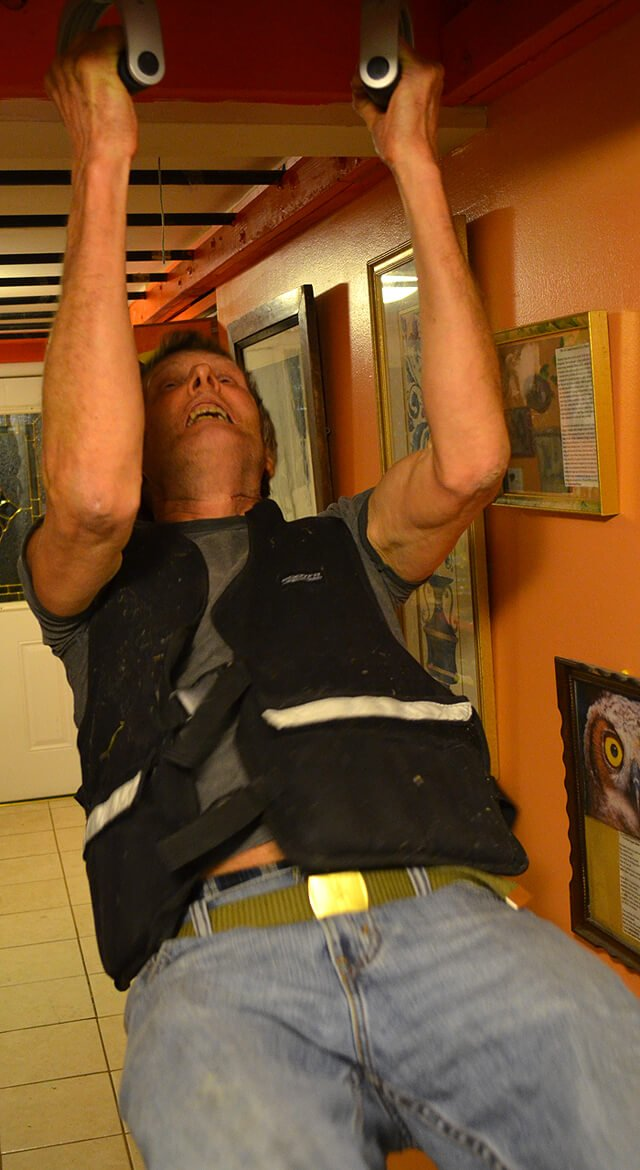 Arnold Kauffman performs chin-ups while wearing a 40-pound vest