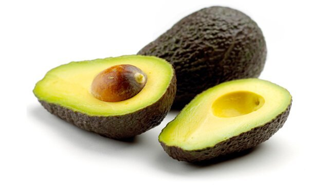 A whole and halved avocado against a white background