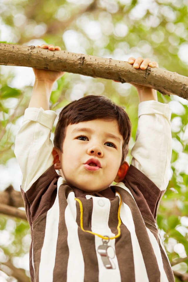 Closeup portrait of a boy hanging on a branch