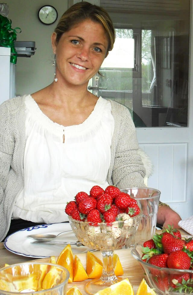 Louise Koch smiles behind a bowl of strawberries on a table