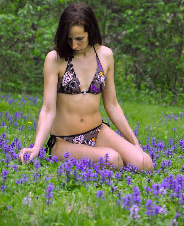 Deanna Husk plays with flowers in a field