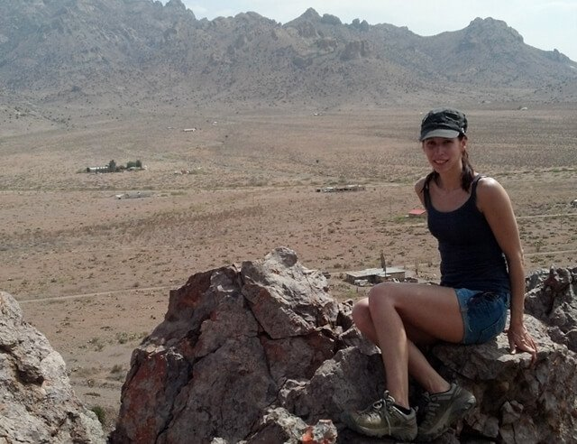 Deanna Husk sits on a rocky looking-out point in New Mexico