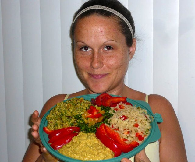 Tasha Lee smiles while holding a platter of raw food