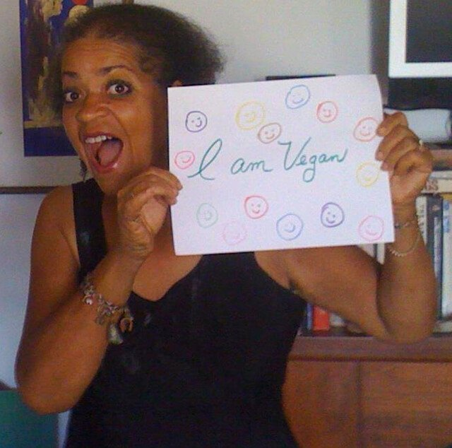 "Toni Allen holds a hand-drawn sign saying, ""I am Vegan."""