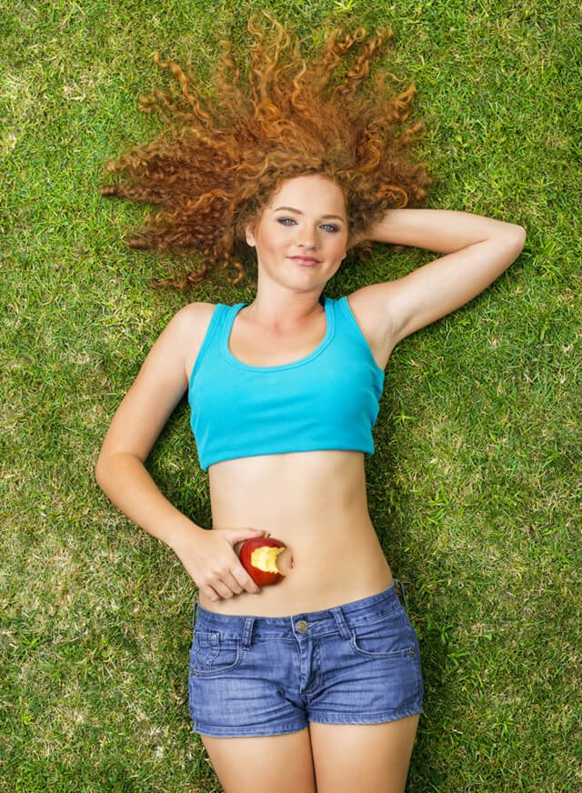 A woman holds a partially chewed apple while resting on grass