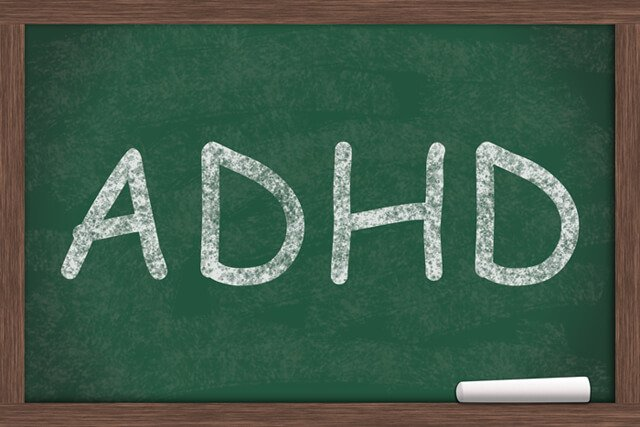 ADHD written in white chalk on a green chalkboard