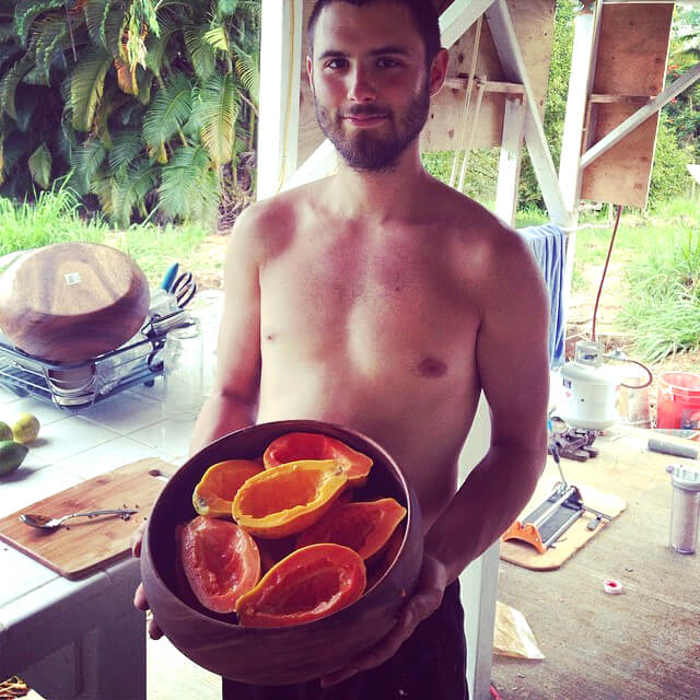 Benjamin Beeler holds a wooden bowl containing papayas in Hawaii