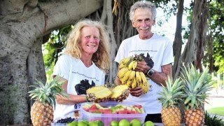 Janette Murray-Wakelin and Alan Murray hold fruits in front of a tableful of fruits