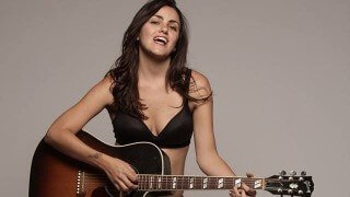 Jesi DiPalo sings and plays guitar in a studio photograph