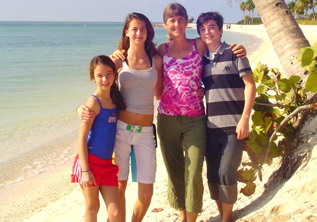 Ellen Livingston poses with her children on a beach