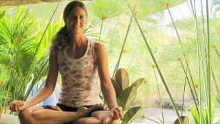 Ellen Livingston smiles while in cross-legged meditation pose