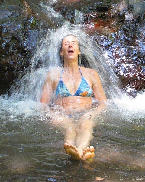 Ellen Livingston getting splashed under a waterfall