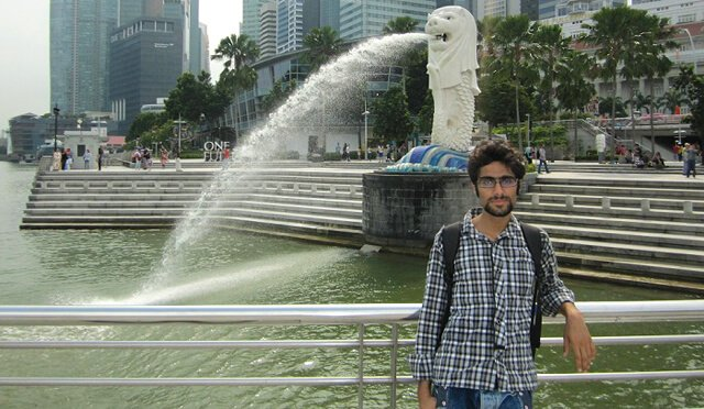 Moein Nejad photographed by a body of water in a city