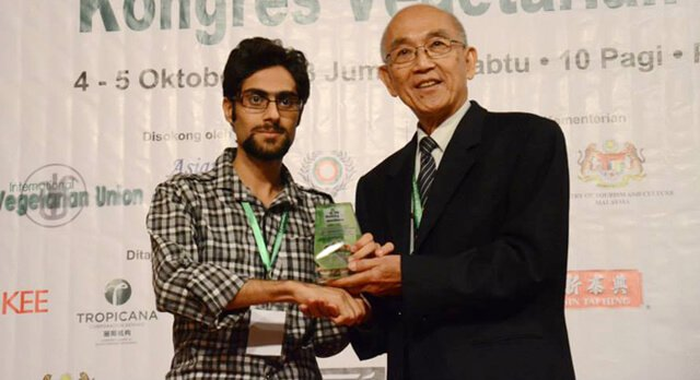 Moein Nejad shakes hands while posing at Vegfest in Malaysia in 2013