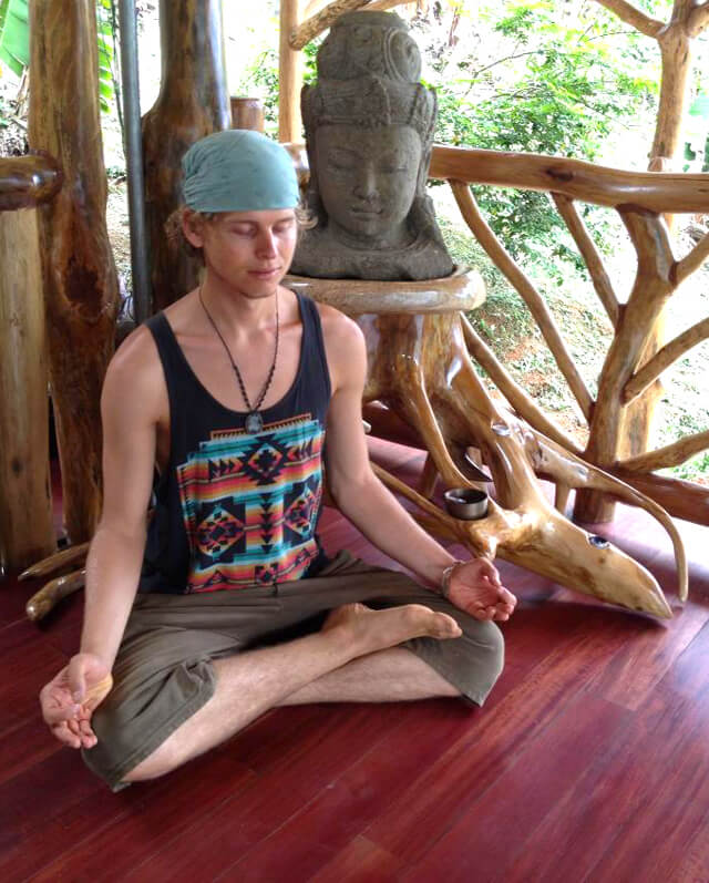Evan Rock meditates beside a statue on a wooden floor