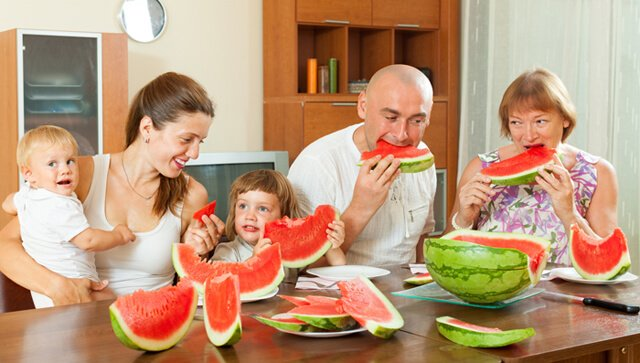Smiling family eats watermelon at home
