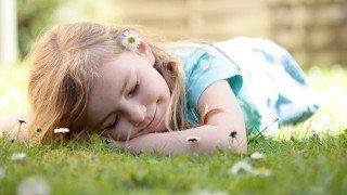 A young girl sleeps on grass