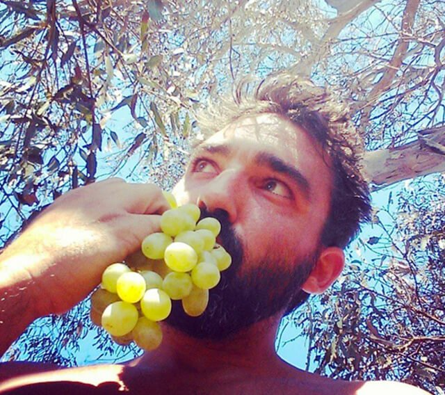"Conor McMillan, a.k.a. ""Handy Man Bananas,"" eats grapes under a tree"