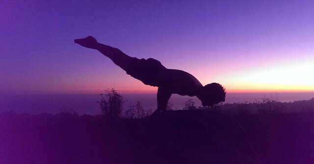 """Conor McMillen, a.k.a. """"Handy Man Bananas,"""" balances while practicing yoga"""