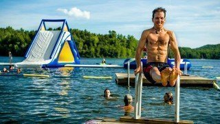 Dr. Samuel Mielcarski flexes by a lake at The Woodstock Fruit Festival