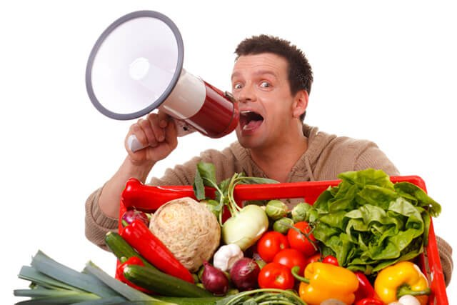 A man speaks into a megaphone adjacent to fruits and vegetables in a large basket