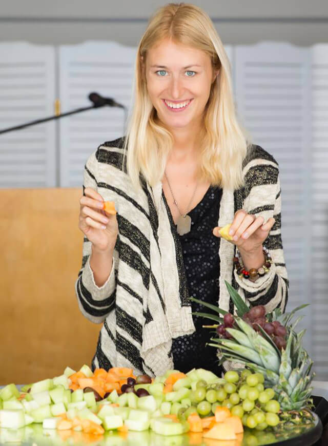 Natalie Lenka holds up freshly cut fruits from a table