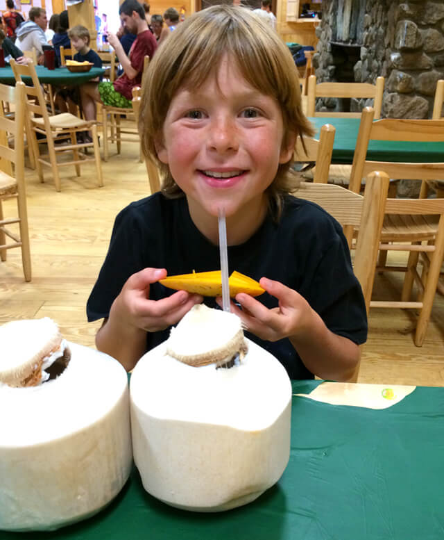 Raw Food Levi eats coconuts and mangos at The Woodstock Fruit Festival after competing in a triathlon