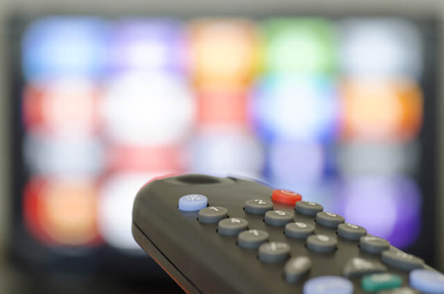 A remote control with a television in the background
