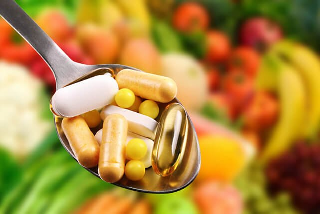 A spoonful of supplements with fruits and vegetables in the background