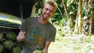 Jason Kvestad is about to chop open a coconut using a machete