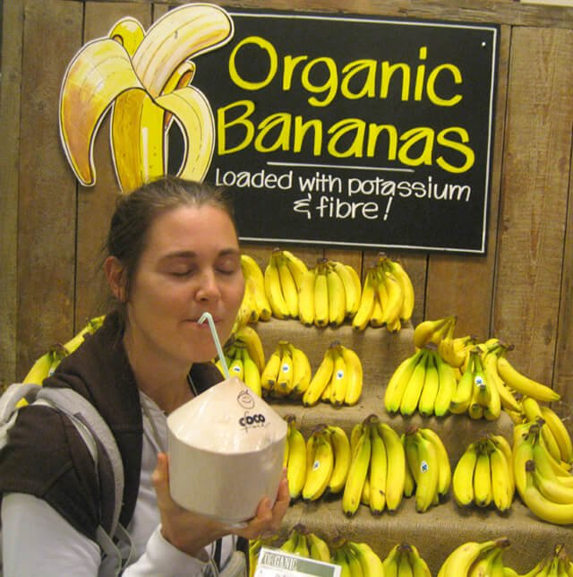 Reny Kattel sips coconut water from a straw beside an organic banana stand