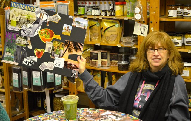 A woman holds up her vision board.