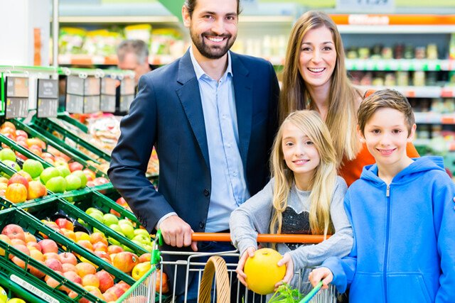 A family shops in a supermarket produce aisle