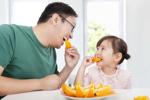 Father and daughter enjoy orange slices