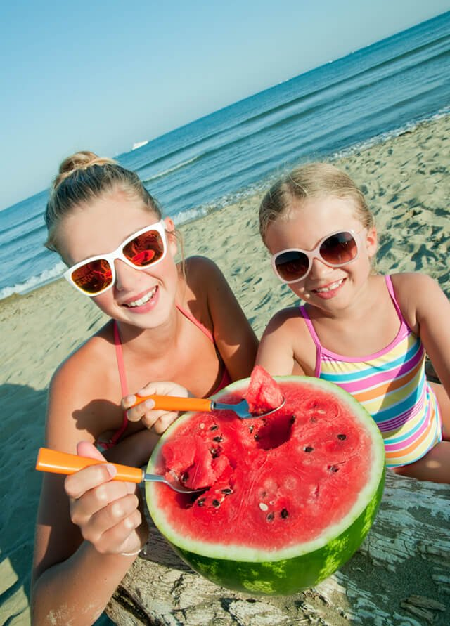 Mother and daughter enjoy watermelon on a beach